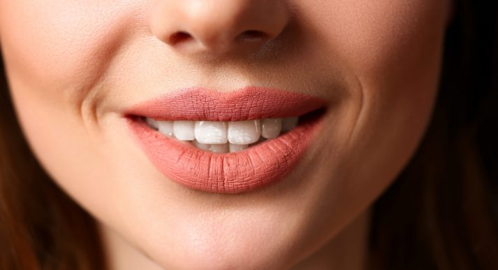 Smiling female closed red lips closeup. Young pretty sexy girl facial oral botox body part hollywood laughing white toothy caries clinic portrait